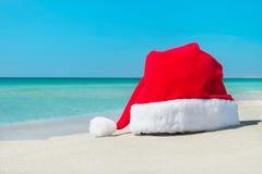 在热带海滩白色沙子的圣诞老人帽子  免版税库存图片