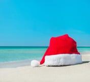 在热带海滩白色沙子的圣诞老人帽子  库存图片