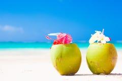 在热带海滩的两个新鲜的椰子鸡尾酒 库存图片