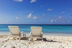 在热带海滩的两张白色轻便折叠躺椅 免版税库存图片