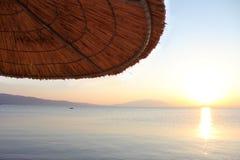 在热带海滩的伞在日落 图库摄影