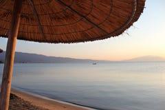 在热带海滩的伞在日落 免版税库存照片