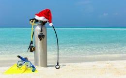 在热带海滩的佩戴水肺的潜水齿轮与圣诞节帽子 免版税库存图片