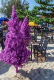 在热带海滩的假圣诞树与椅子和桌 免版税库存照片