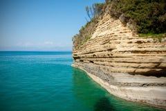 在热带海滩的剧烈的峭壁用绿松石水 库存照片