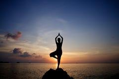 在热带海滩的剪影少妇凝思实践的瑜伽姿势 免版税图库摄影
