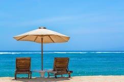 在热带海滩的太阳懒人与伞 免版税库存照片