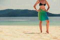 在热带海滩的妇女佩带的布裙 免版税库存图片