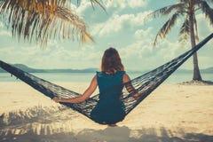 在热带海滩的妇女坐的oin吊床 免版税库存照片