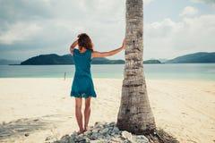 在热带海滩的妇女支持的棕榈树 免版税库存图片