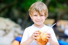 在热带海滩的小孩男孩饮用的椰子汁 库存图片