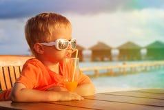 在热带海滩的小男孩饮用的鸡尾酒 图库摄影