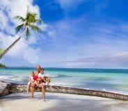 在热带海滩的愉快的微笑的家庭和 免版税库存照片
