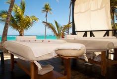 在热带海滩的按摩桌 库存图片