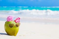 在热带海滩的新鲜的椰子鸡尾酒与花 免版税库存图片
