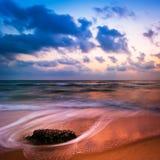 在热带海滩的日落。在海洋海岸的岩石 库存照片