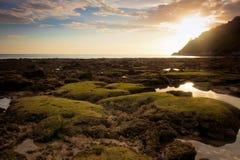 在热带海滩的日落与岩石和石头 免版税库存照片