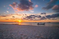 在热带海滩的日落在Isla Mujeres,墨西哥 免版税库存图片