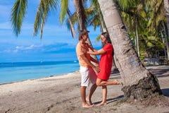 在热带海滩的浪漫夫妇在棕榈树附近 免版税库存照片