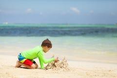 在热带海滩的白种人男孩大厦沙子城堡 图库摄影