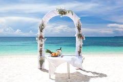 在热带海滩的美丽的婚礼曲拱 免版税库存照片