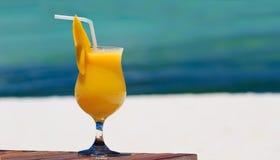 在热带海滩的芒果鸡尾酒 库存照片