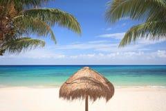 在热带海滩的草伞 库存图片