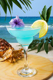 在热带海滩的蓝色夏威夷鸡尾酒 免版税库存照片