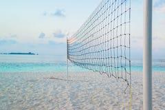 在热带海滩的被撕毁的沙滩排球网 免版税库存照片