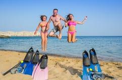 在热带海滩的跳跃的家庭 库存照片