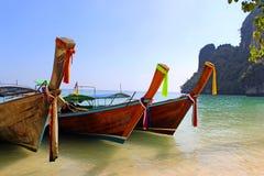 在热带海滩的长尾巴小船 免版税库存图片