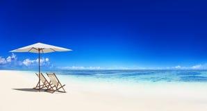在热带海滩的轻便折叠躺椅 库存照片