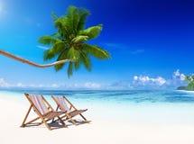在热带海滩的轻便折叠躺椅 图库摄影