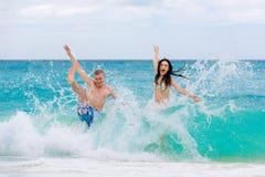 在热带海滩的年轻爱恋的愉快的夫妇 免版税库存照片