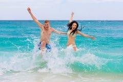 在热带海滩的年轻爱恋的愉快的夫妇 图库摄影