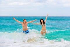 在热带海滩的年轻爱恋的愉快的夫妇 库存照片