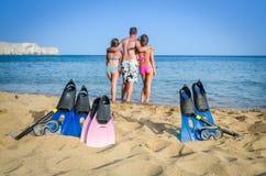在热带海滩的活跃家庭 图库摄影
