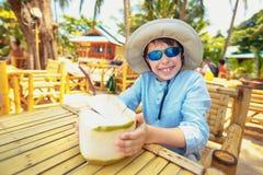 在热带海滩胜地的小男孩饮用的椰子鸡尾酒 免版税库存照片