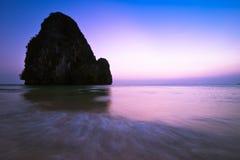 在热带海滩风景的日落 与岩石格式的海洋海岸 免版税库存照片