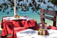 在热带海滩餐馆制表与瓶的设置橄榄油和醋 库存照片