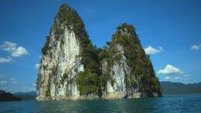 在热带湖、山、峭壁和岩石湖水的小船旅行在日落期间 股票录像