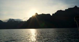 在热带湖、山、峭壁和岩石湖水的小船旅行在日落期间 影视素材
