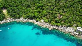 在热带火山岛附近的风平浪静 蓝色海和绿色密林平安的水寄生虫视图在石岸附近的  影视素材