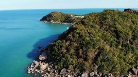 在热带火山岛附近的风平浪静 蓝色海和绿色密林平安的水寄生虫视图在石岸附近的  股票录像