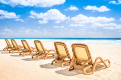 在热带空的海滩和绿松石海的Sunbeds躺椅 库存照片
