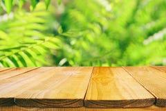 在热带绿色花卉背景前面的木桌 对产品显示和介绍 免版税库存图片
