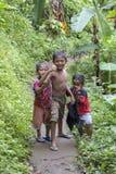 在热带街道上的愉快的三个年轻男孩在海岛巴厘岛,印度尼西亚 免版税库存照片