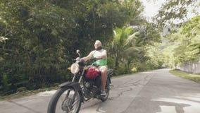 在热带路的成人人骑马摩托车在绿色高地环境美化 领抚恤金者人骑马摩托车一会儿moto 影视素材