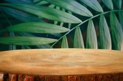 在热带绿色花卉背景前面的木桌 对产品显示和介绍 库存照片