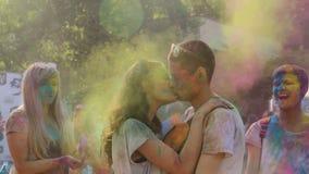 在热情地亲吻在明亮的粉末云彩的颜色节日的爱的夫妇  股票视频